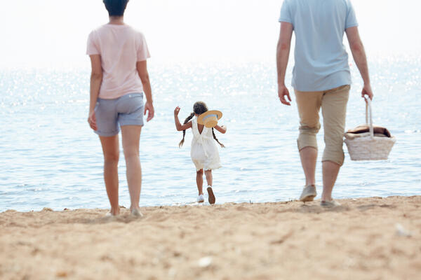 family-arriving-to-beach-C36NYRD