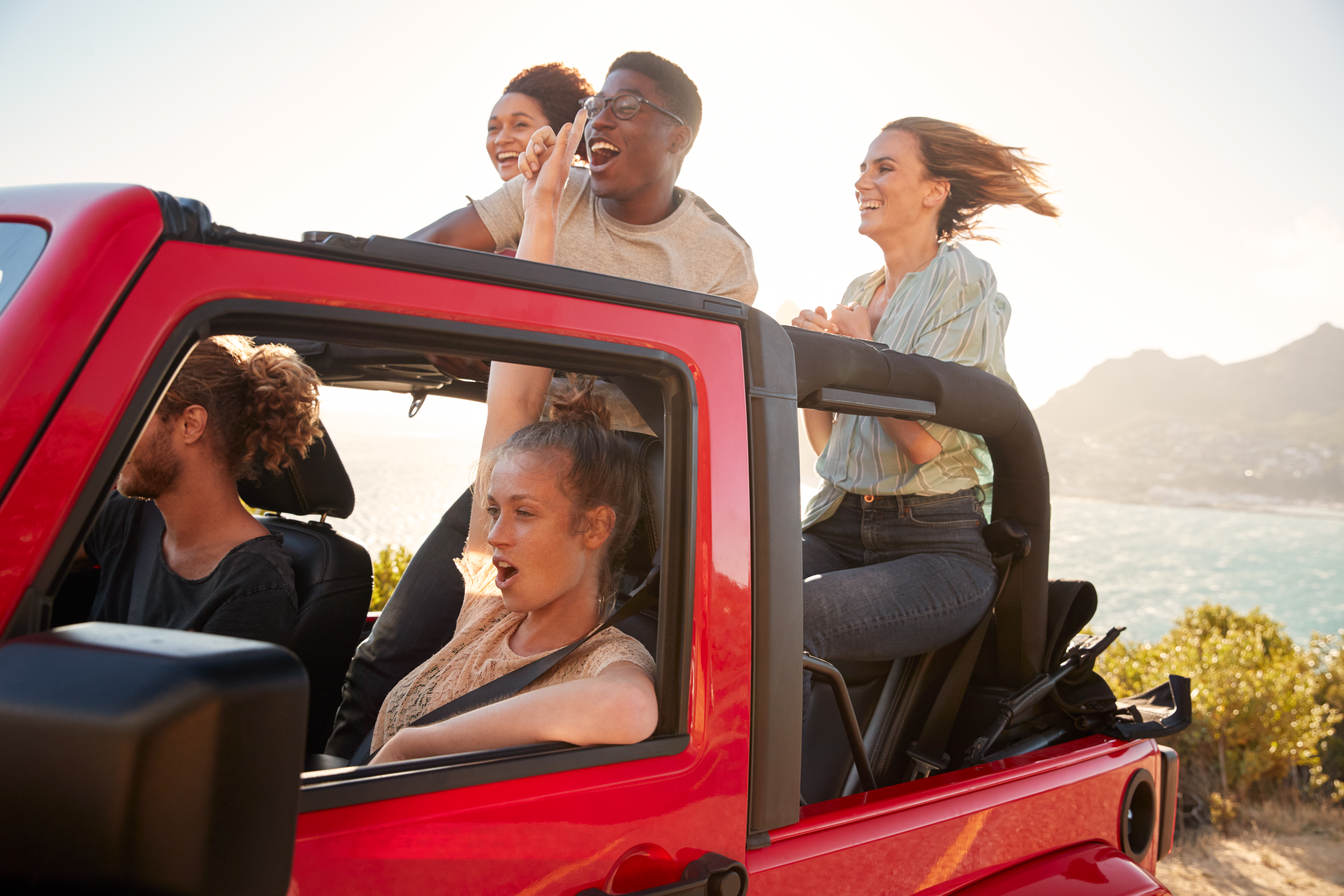 five-young-adult-friends-on-a-road-trip-driving-in-RA725T3