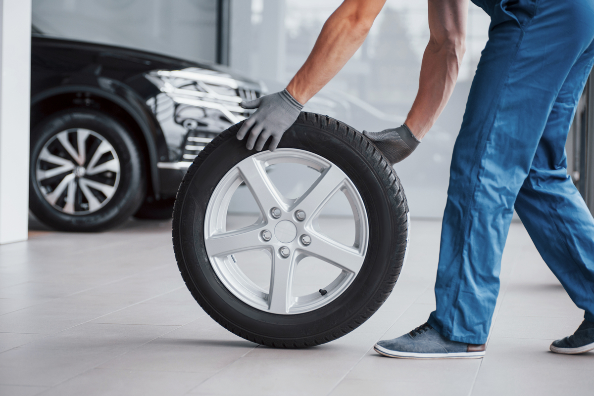 mechanic-holding-a-tire-tire-at-the-repair-garage--BBTJS9B