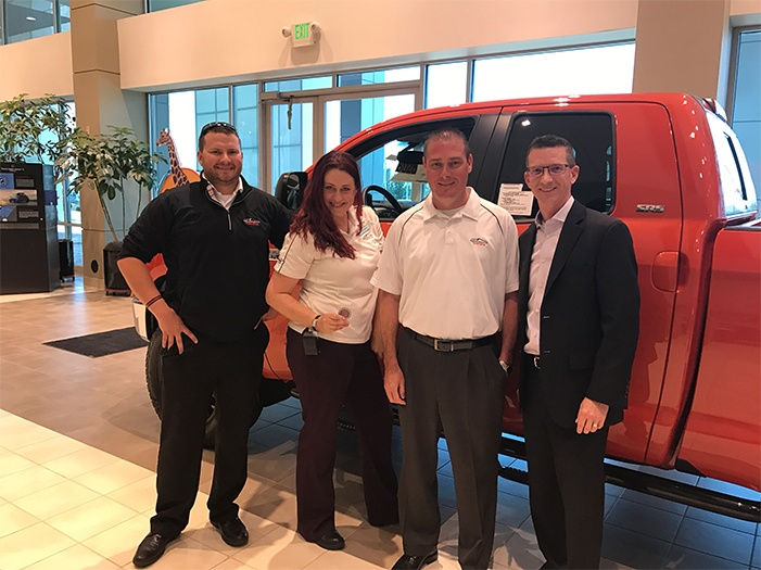 Sales Representative Christian Janzen, far left, Sales Representative Jen Decker, holding the coin, and General Sales Manager Sean Kramer, third from left, proudly accept the Insignia challenge coin from Insignia President David Stringer, April 12, at Mountain States Toyota, in Denver, CO.