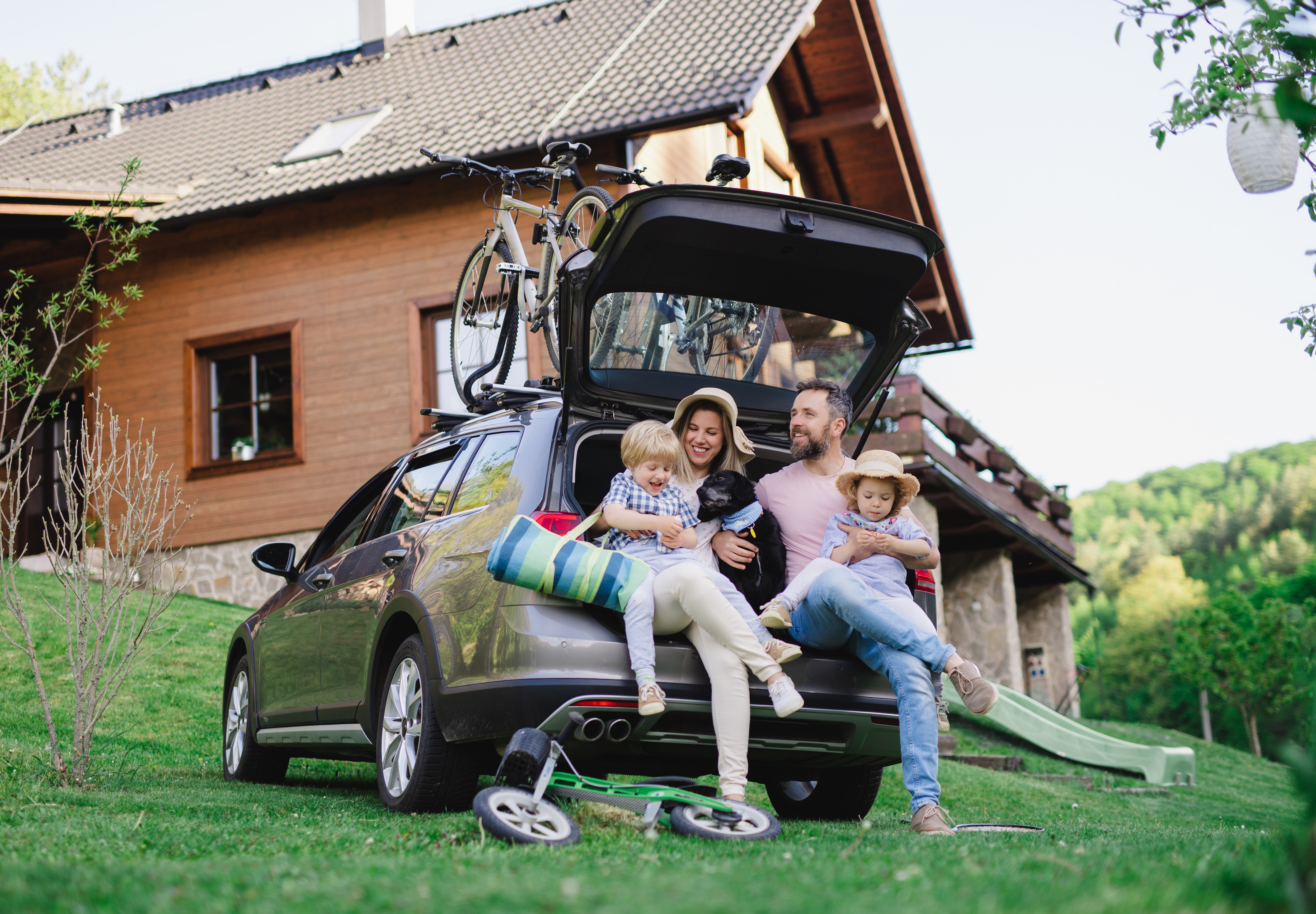 family with packed car and bikes