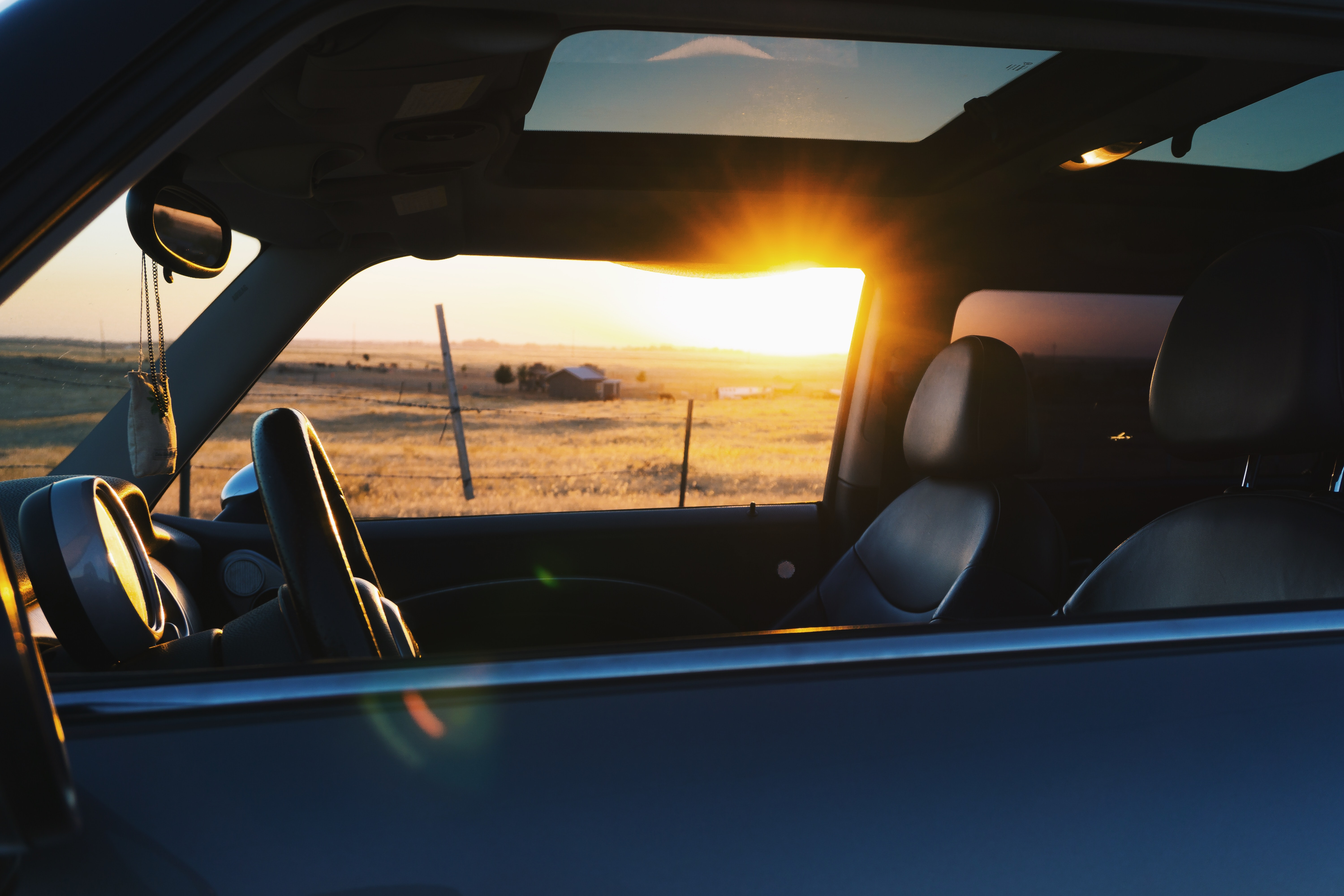 car with sunroof and sunset
