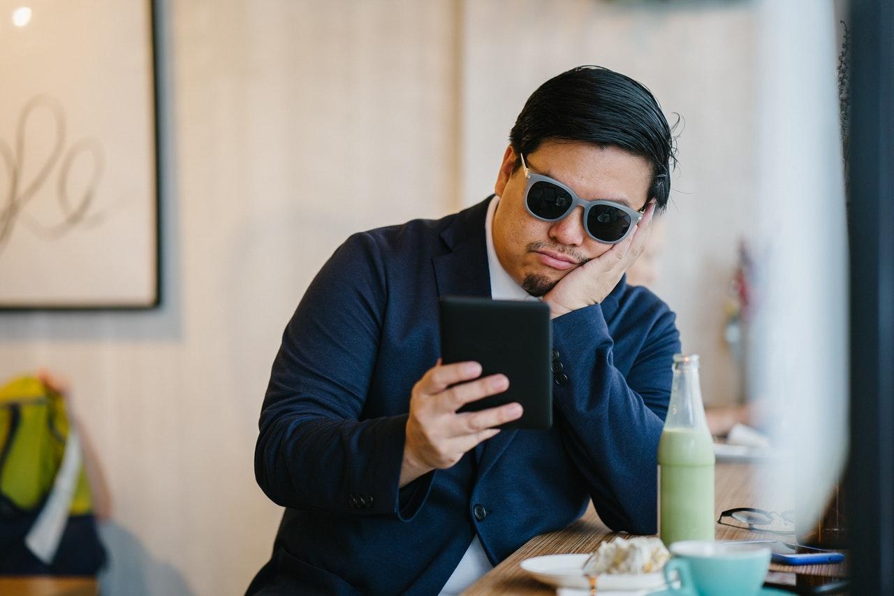 bored man looking at phone
