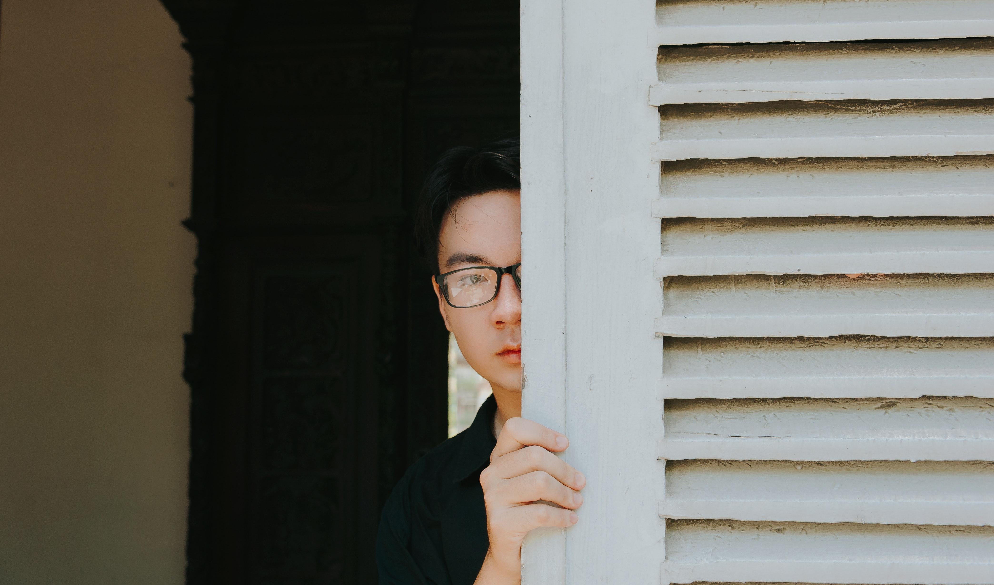 man hiding behind door